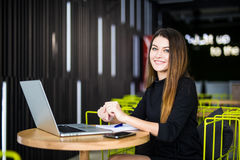 Happy smiling woman working with laptop in modern smart space hub Stock Image