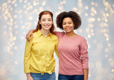 Happy smiling women hugging over holidays lights Royalty Free Stock Photos