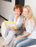 Happy smiling women looking at photo frame Stock Photography