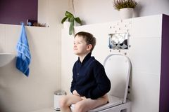 Happy smiling 6 year old boy sitting on the toilet. Dressed in a dark navy blue woolen sweater royalty free stock photography