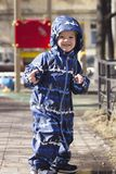 Happilly smiling 2-year-old child outdoor in the spring. Photo of  a happy  boy, two years old, wearing dark blue coveralls. Concept of happy childhood, playing Royalty Free Stock Image