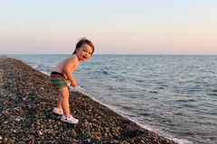 Happy smiling 2 years boy standing on the pebbles beach at sunse Royalty Free Stock Photos