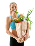 Happy smiling youing woman with lettuce in her mouth and grocery bag full of healthy fruits and vegetables Royalty Free Stock Photography