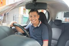 Driver in his car. Happy smiling young asian driver looking at camera while sitting in his car Stock Photo