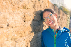 Happy smiling young asian teenager girl leaning against stone wa Royalty Free Stock Image