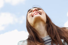 Happy smiling young attractive woman over blue sky Royalty Free Stock Photography