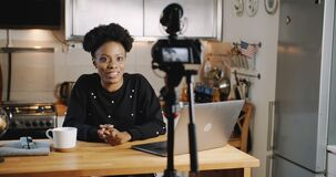 Happy smiling young beautiful black vlogger woman filming new video using professional camera at home table slow motion.