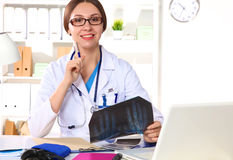 Happy smiling young beautiful female doctor showing blank area for sign or copyspace,  over white background Stock Photos