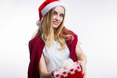 Happy smiling young blond woman wearing red Santa hat and giving Christmas gift box on white background stock photography