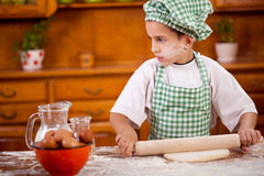 Happy smiling young boy chef in kitchen making dough with rollin Stock Photo