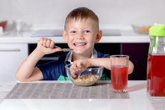 Happy smiling young boy eating his lunch Stock Photography