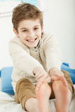 Happy smiling young boy stretching for his toes. Happy smiling young boy sitting on his bed stretching for his bare toes with a cute grin as he looks at the Stock Photos