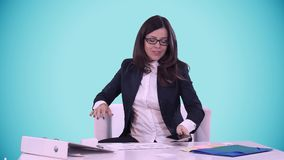 Happy smiling young brunette in a business suit shows thumb on the camera. She sits in the office behind a Desk. stock video footage