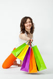 Happy smiling young brunette in orange pants showing multicolore Royalty Free Stock Photography
