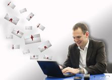 Happy smiling businessman using laptop in office for letters Royalty Free Stock Images