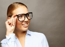 Happy smiling young business woman in glasses, over grey backgr royalty free stock images