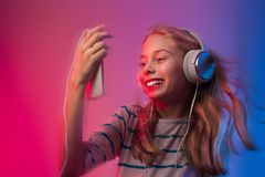 Girl with smartphone and headphones listens to music Royalty Free Stock Images