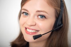 Happy smiling young caucasian woman with headset phone in a call center or office, close up stock images