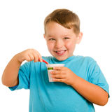 Happy smiling young child eating yogurt stock photo