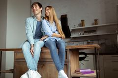 Happy smiling young couple in blue denim cloth sitting in the kitchen royalty free stock image