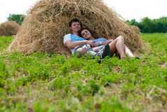 Happy smiling Young couple & haystack Royalty Free Stock Image