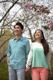 Happy smiling young couple holding hands in the park in springtime, three quarter length Stock Photography