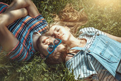 Happy smiling young couple lying on grass in the field Stock Photo