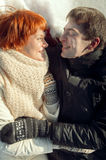 Happy smiling young couple lying on snow and looking to each oth Royalty Free Stock Photo