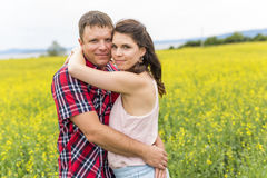 Happy smiling young couple over yellow green rape meadow Stock Photography