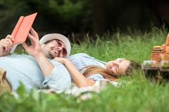 Happy smiling young couple relaxing in a park. Lying on a picnic blanket royalty free stock photo