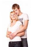 Happy smiling young couple standing together hugging Stock Images