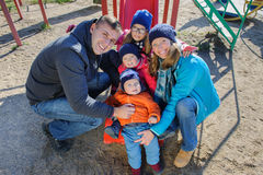 Happy smiling young family of five at children`s playground in park Stock Photo