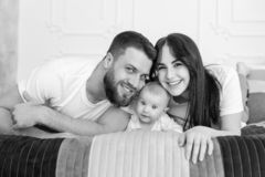 Happy smiling young family portrait in bedroom. Father, mother and baby girl in white outfit lay and pose. Happy smiling young family portrait in bed. Black and stock image