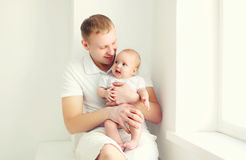 Happy smiling young father and baby home in white room near window Royalty Free Stock Photo