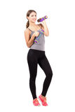 Happy smiling young female posing while holding dumbbells looking at camera Royalty Free Stock Photo