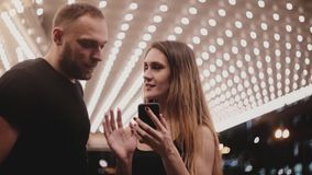 Happy smiling young friends, man and woman, standing in amazing Chicago theater using smartphone talking to each other. stock footage