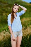 Happy young girl in the field. Happy smiling young girl in blue shirt and shorts in the field royalty free stock image