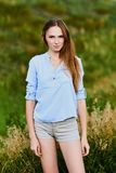Happy young girl in the field. Happy smiling young girl in blue shirt and shorts in the field royalty free stock photography