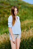 Happy young girl in the field. Happy smiling young girl in blue shirt and shorts in the field royalty free stock photos