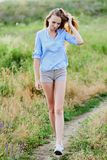 Happy young girl in the field. Happy smiling young girl in blue shirt and shorts in the field royalty free stock images
