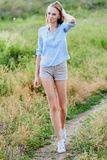 Happy young girl in the field. Happy smiling young girl in blue shirt and shorts in the field stock photo