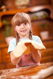Happy smiling young girl chef in kitchen making dough Stock Image