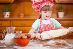 Happy smiling young girl chef in kitchen making dough Royalty Free Stock Image