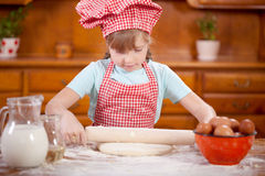 Happy smiling young girl chef in kitchen making dough Royalty Free Stock Photos
