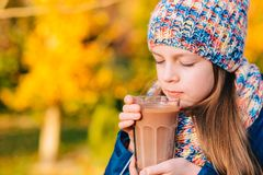 Happy smiling young girl drinking chocolate Royalty Free Stock Photography