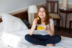 Happy smiling young girl eating snack and enjoying Stock Images