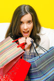 Happy smiling young girl holding shopping bags full of clothes Stock Photo