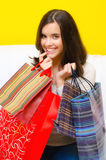 Happy smiling young girl holding shopping bags full of clothes Royalty Free Stock Photography