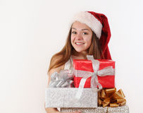 Happy smiling young girl in Santa hat with gifts for Christmas Stock Images