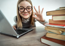 Happy smiling young girl showing okay gesture while using her laptop computer Stock Image